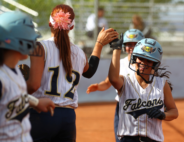 Foothill's Vanessa Parrales high fives teammate Sarah Maddox (12) after scoring a run against Coronado on Wednesday. The Falcons won, 8-7. (Chase Stevens/Las Vegas Review-Journal)