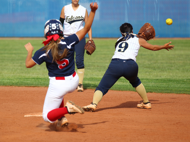 Foothill's Alexia Campbell (9) reaches for a throw as Coronado's Nicole Hardy (5) slides safely into second on Wednesday. The Falcons won, 8-7. (Chase Stevens/Las Vegas Review-Journal)