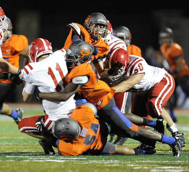 Brophy Prep quarterback Cade Knox (11) is tackled by Bishop Gorman linebacker Ikem Okeke, right, and defensive tackle C.J. Nedd in the first half of the Sollenberger Classic on Aug. 22. (Josh Holm ...