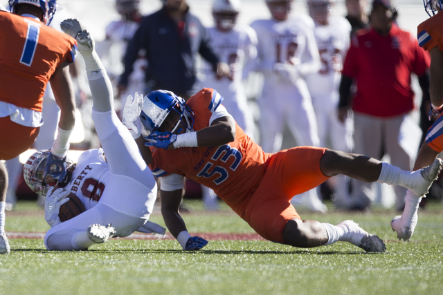Liberty's Bryson Delacruz (8) is tackled by Bishop Gorman's Farrell Hester (53) after a run in the Class 4A state football championship game at Sam Boyd Stadium on Saturday, Dec. 3, 2016, in Las V ...