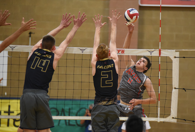 Arbor View's Treven Clizbe (11) spikes the ball against Foothill's Jonny Rolle (14) and Mason Hansen (2) during their Division I state volleyball semifinals played at Legacy High School in North L ...
