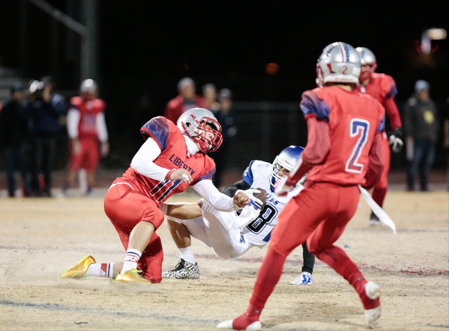 Basic's Dallon Ellett (88) is knocked back by Liberty's Preston Pavlica (11) during the first half of the Sunrise Region championship game at Liberty on Friday. Ellett made seven catches for 45 ya ...