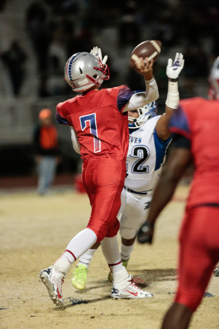 Liberty's Kenyon Oblad (7) throws a pass as Basic's John Funaki (22) attempts to knock it down half during the Sunrise Region championship game at Liberty on Friday. Oblad completed 10 of 18 passe ...