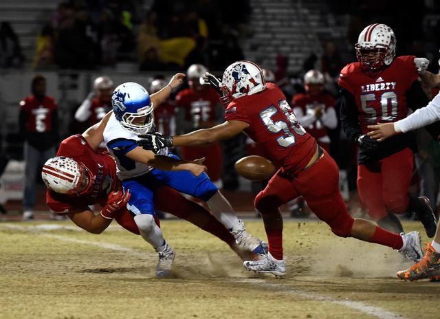 Basic quarterback Rasheem Newsome (8) fumbles the ball under pressure from Liberty during a high school football game at Liberty High School Friday, Nov. 18, 2016, in Henderson. David Becker/Las V ...