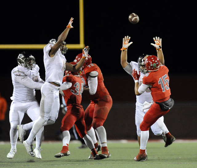 Bishop Gorman's Ethan Palelei, right, and Alize Jones (8) rush Arbor View quarterback Bryce Poster (15) during the first half of the Sunset Region championship game at Arbor View on Friday. Poster ...
