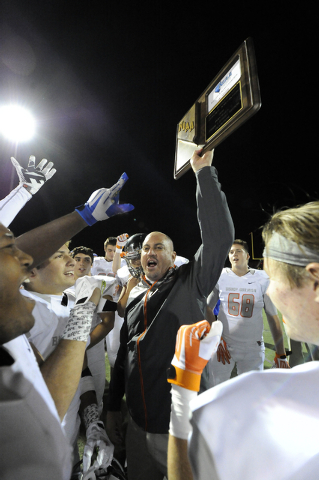 Bishop Gorman head coach Tony Sanchez, center, hoists the Sunset Region championship trophy with players after their 56-6 win over Arbor View during the Sunset Region championship game at Arbor Vi ...