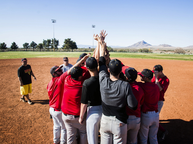 Tech baseball coach Bill Stuber, left, watches his team huddle during practice at the Silver Bowl park baseball field near Sam Boyd Stadium. Tech's sports teams have to practice and play at remote ...