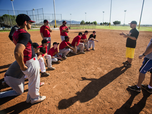 Tech baseball coach Bill Stuber, right, talks to his team during practice at the Silver Bowl park baseball field near Sam Boyd Stadium on Monday. Tech's sports teams have to practice and play at r ...