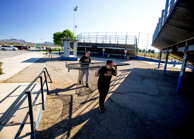 Tech junior varsity baseball players Casey Brokaw, 15, and Mathew O'Keefe carry a batting cage after practice at the Silver Bowl park baseball field near Sam Boyd Stadium on Monday. Tech's sports  ...