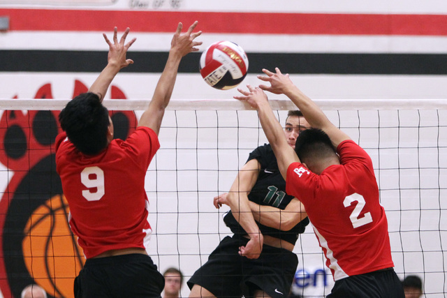Palo Verde's Michael Simister nails a shot between Las Vegas' Ronell Sueno, left, and Royce Reyes during their Division I state volleyball semifinal Tuesday, May 12, 2015 at Las Vegas High. Palo V ...