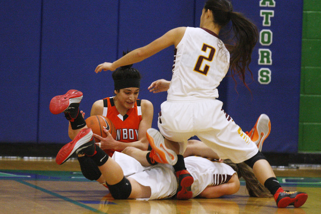 Chaparral guard Abigail Delgado falls over Dimond guard Nikki Forrey during the Gator Winter Classic  Wednesday at Green Valley High School. Delgado had 13 points, but Dimond won the game in overt ...
