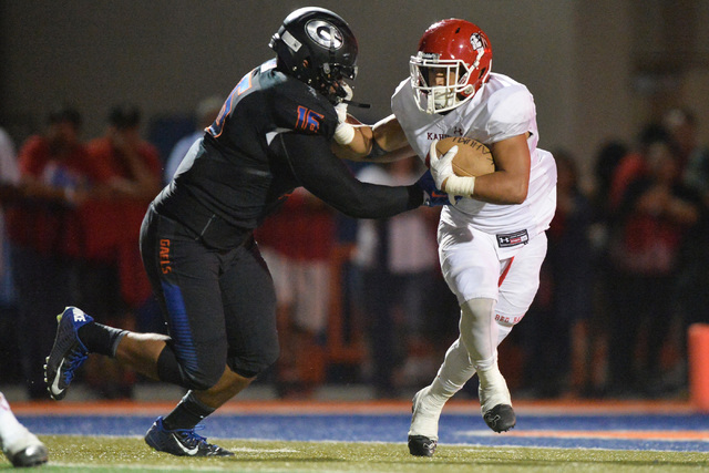 Kahuku running back Elvis Vakapuna (42) stiff arms Bishop Gorman defensive lineman Haskell Garrett (16) during the Bishop Gorman High School Kahuku High School game at Bishop Gorman in Summerlin o ...