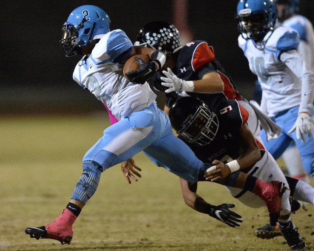 Canyon Springs junior Diamante Burton (2) tries to break a tackle from Las Vegas senior T.J. McGary (9) during the Las Vegas High School Canyon Springs High School game at Las Vegas High School on ...