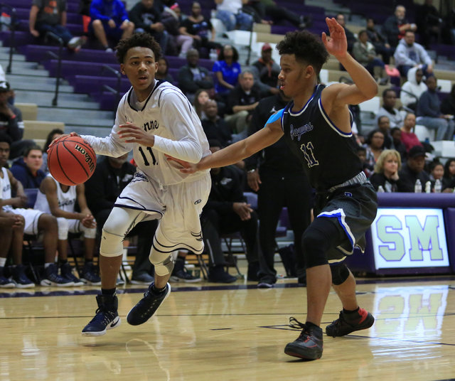Cheyenne freshman Ke'Shawn Hall (11) dribbles the ball around a defender during the Class 3A boys regional basketball final between Desert Pines High School and Cheyenne High School at Sunrise Hig ...