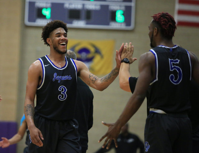 Desert Pines senior Trevon Abdullah (3) smiles as he is pulled off the court in the fourth quarter of the Class 3A boys regional basketball final between Desert Pines High School and Cheyenne High ...