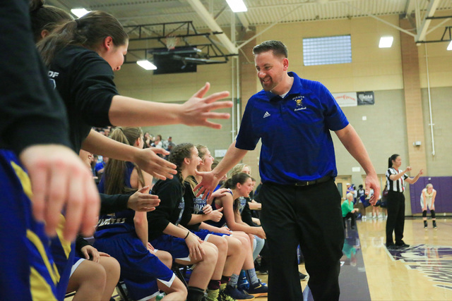Moapa Valley head coach Stuart Humes high-fives his team before time runs out during the Class 1A girls regional basketball final between Moapa Valley High School and Virgin Valley High School at  ...