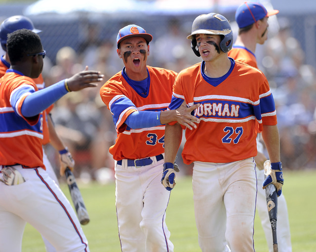 Bishop Gorman's Grant Robbins (27) is congratulated by teammates after scoring a run in the top of the seventh on Saturday. Gorman left two runners on in the seventh, and Centennial held on for a  ...