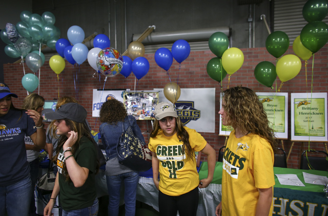 Arbor View softball players and triplets, from left, Bryce, Breanne, and Brittany Henricksen look around as Las Vegas area high school softball players gather to sign their national letters of int ...