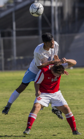 Canyon Springs senior defender Alejandro Reveles (4) fights for a header with Arbor View junior midfielder Nicklaus Dongmannon (12) on Tuesday, Sept. 6, 2016, at Canyon Springs High School in Las  ...