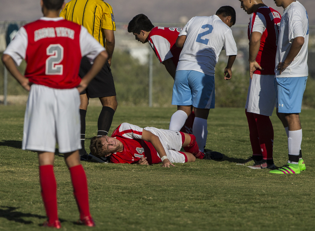 Arbor View junior midfielder Zachary Breaz (14) waits for medical attention after colliding with a Canyon Springs defender on Tuesday, Sept. 6, 2016, at Canyon Springs High School in Las Vegas. Th ...