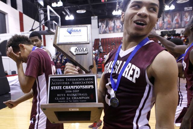 Agassi Prep's Allen Merritt (5), right, holds the championship trophy after him and his team won a Class 2A boys state final at the Cox Pavilion on Saturday, Feb. 25, 2017, in Las Vegas. Agassi Pr ...