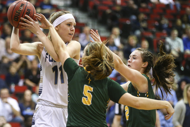 Bishop Manogue guard Malia Holt (C) (5) and forward Maddie Camacho (2) defend against Foothill's Kylie Vint (11) during the Class 4A girls state basketball semifinals at the Cox Pavilion in Las Ve ...