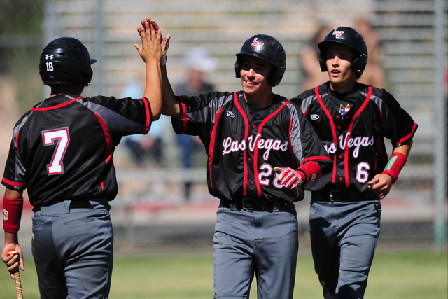Las Vegas base runner Diego Delgado high fives Payton Miller (7) after scoring on a single hit by Ryan Freimuth (6), who also scored on the play in the first inning of their prep baseball game aga ...