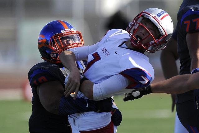 Bishop Gorman middle linebacker Nela Otukolo (10) wraps up Liberty quarterback Kenyon Oblad (7) after Oblad threw a pass in the Division I state football semifinal game at Rancho on Nov. 29. Otuko ...