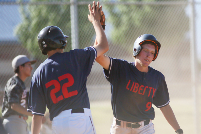 Liberty's Michael Wong left, and Jacob Klein slap hands as Klein scores a run during a baseball game against Las Vegas at Liberty High School Tuesday, April 21, 2015, in Las Vegas. Liberty won 6-3 ...
