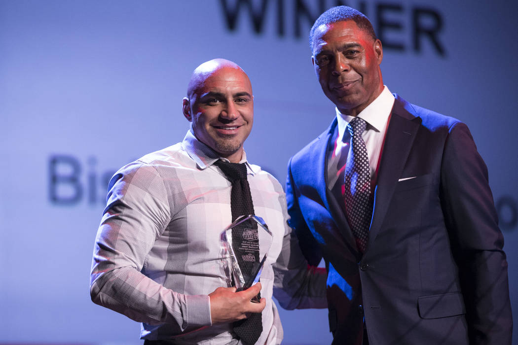 Kenny Sanchez, left, head coach for the Bishop Gorman High School football team, is presented with the Team of the Year Award by football hall of famer Marcus Allen during the annual Best of Nevad ...