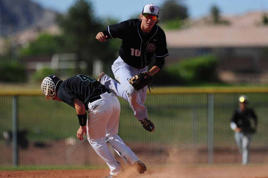 Palo Verde base runner Dylan Orlando (4) interferes with Desert Oasis shortstop Bryson Stott while Stott tries to turn a double play in the third inning of their prep baseball game at Palo Verde H ...