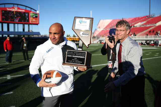 Bishop Gorman's head football coach Kenny Sanchez is presented the champion trophy by Bart Thompson, executive director for the Nevada Interscholastic Activities Association, after their 84-8 win  ...