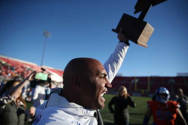 Bishop Gorman's head football coach Kenny Sanchez lifts the champion after their 84-8 win against Liberty in the Class 4A state football championship game at Sam Boyd Stadium on Saturday, Dec. 3,  ...