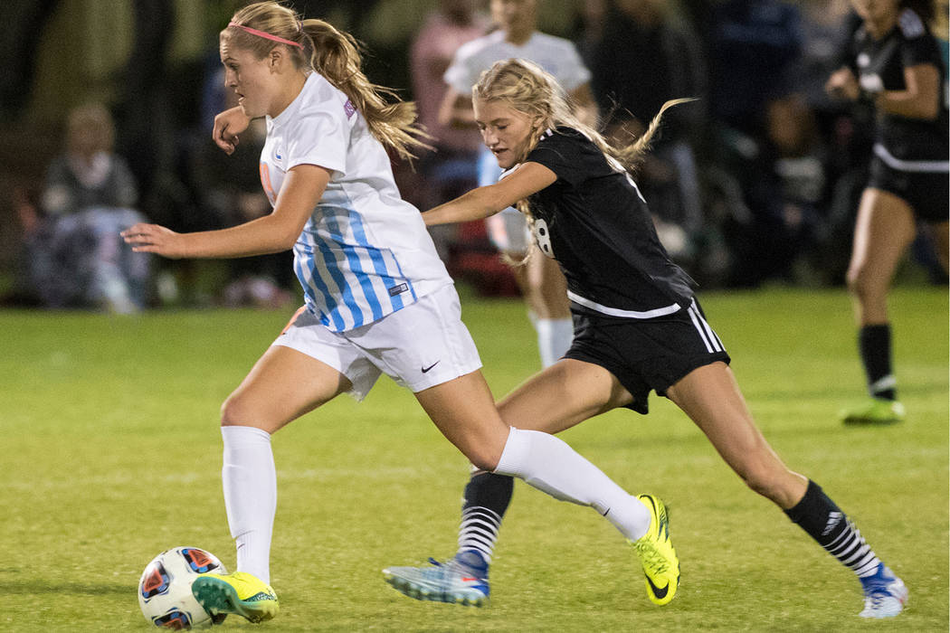 Arlie Jones (19), from Bishop Gorman High School, battles for the ball against Alexis Lloyd (8), from Palo Verde School, during the Sunset Region girls soccer semifinal game at Bettye Wilson Socce ...