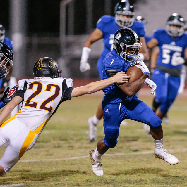 Pahrump Valley senior Drew Walker (22) reaches out for Desert Pines senior Isaiah Morris (7) as he attempts to stop him from moving up field during a varsity football matchup at Desert Pines High  ...