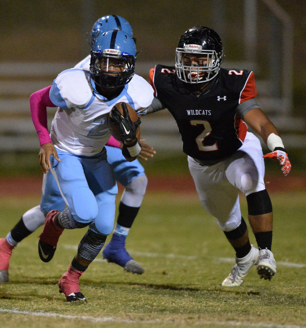 Canyon Springs junior Diamante Burton (2) runs away from Las Vegas linebacker Cruz Littlefield (2) during the Las Vegas High School Canyon Springs High School game at Las Vegas High School on Frid ...