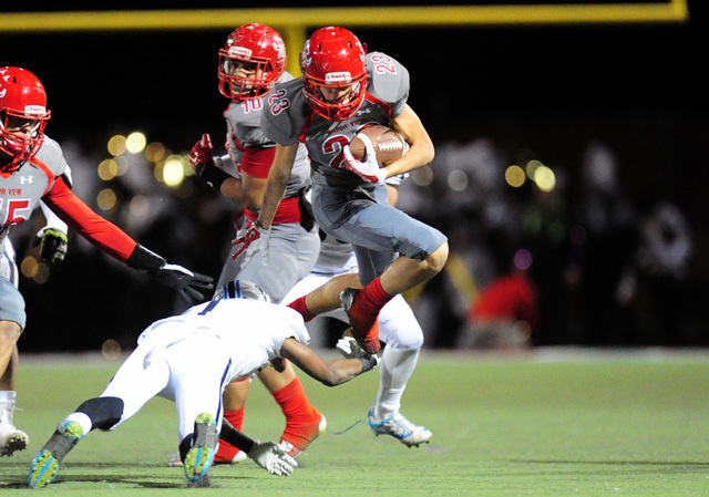 Arbor View running back defensive back Deago Stubbs jumps over Centennial cornerback Demetrius Goodman (1) in the first half of their prep football game at Arbor View High in Las Vegas Thursday, O ...