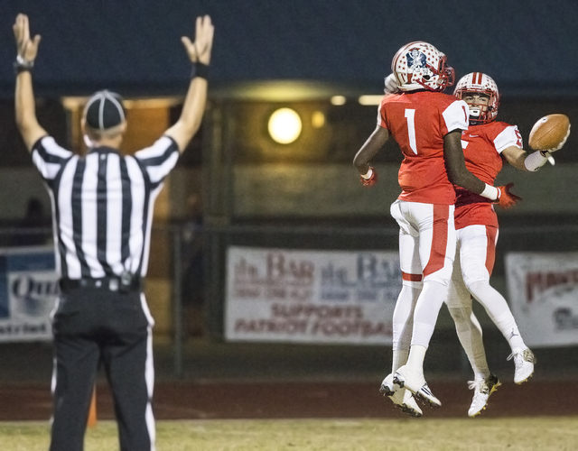 Liberty's Ethan Dedeaux (5) celebrates a first quarter touchdown with teammate Marquez Powell (1) during the Sunrise Region semifinal game on Thursday, Nov. 10, 2016, at Liberty High School in Hen ...