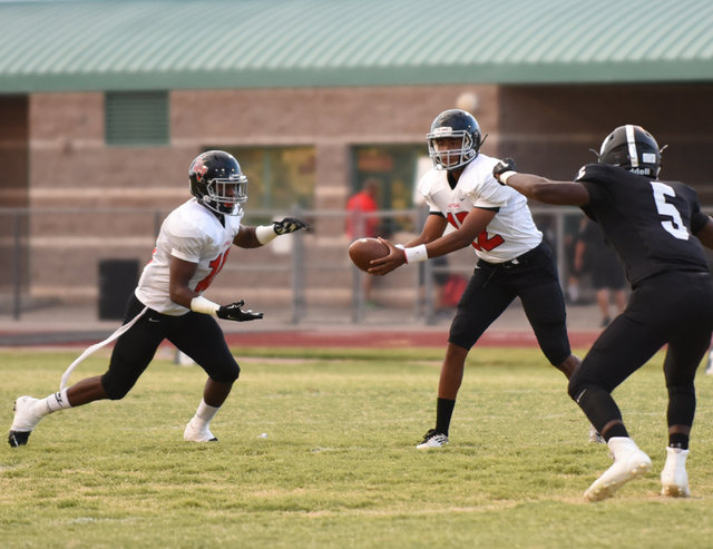 Las Vegas High School's Zach Matlock (12) hands off the football to teammate Elijah Hicks (10) against Palo Verde's defense during their football game played at Palo Verde's football field in Las  ...