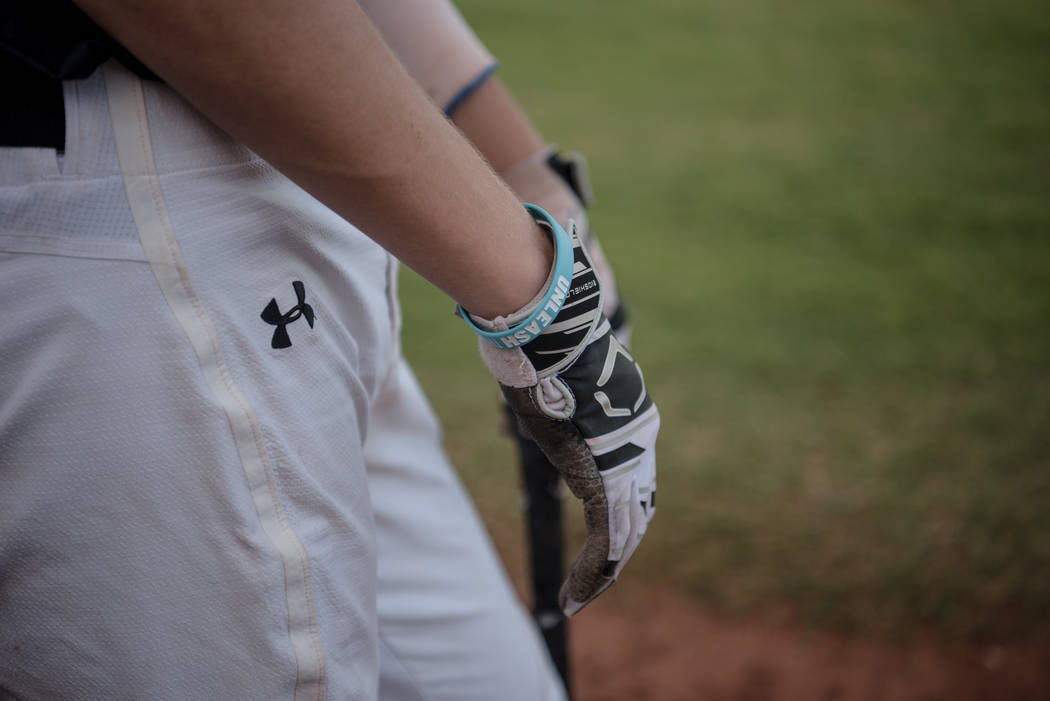 "An ""Unleash"" bracelet on Faith Lutheran Crusader Paulshawn Pasqualotto, waiting for his turn to bat during a game at Faith Lutheran High School on Thursday, July 6, 2017, in Las  ..."