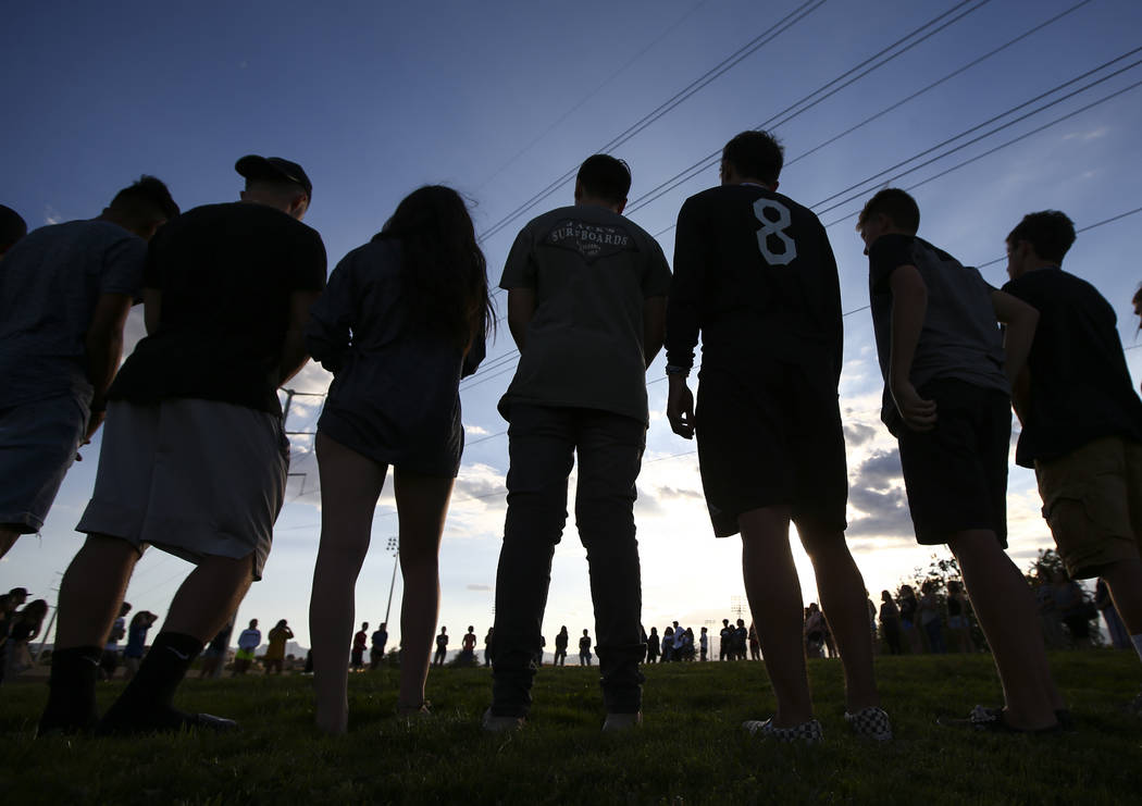 People stand in a circle during a vigil for Haylei Hughes, a former Cimarron-Memorial student-athlete, who died in a hiking accident in Wash., at Kellogg Zaher Sports Complex in Las Vegas on Thurs ...