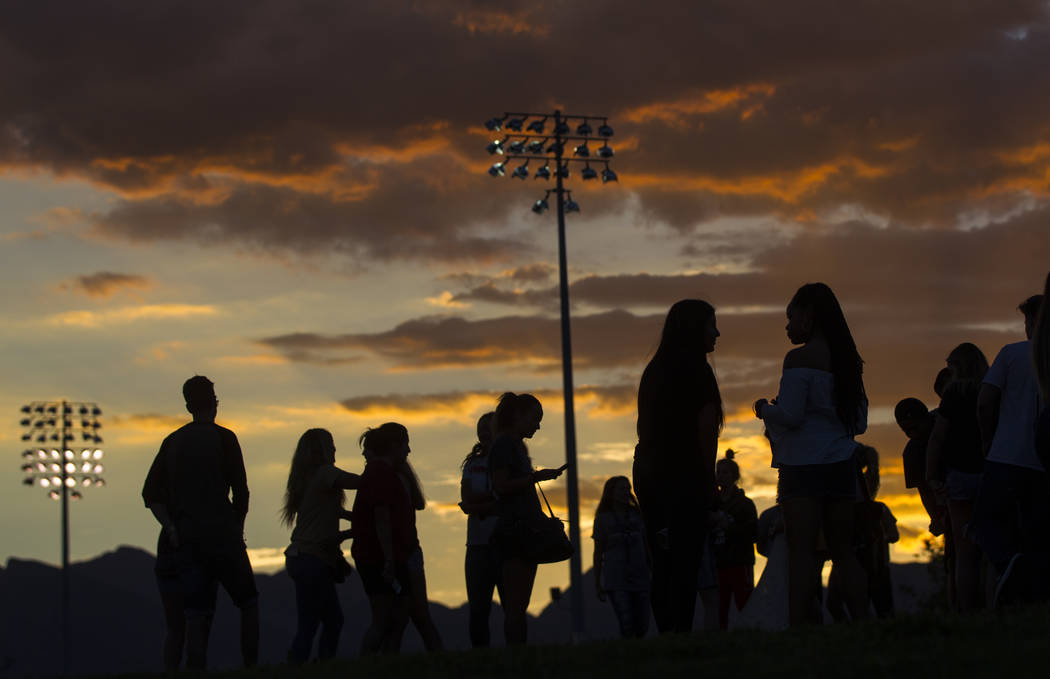 People are silhouetted against the sky after a vigil for Haylei Hughes, a former Cimarron-Memorial student-athlete, who died in a hiking accident in Wash., at Kellogg Zaher Sports Complex in Las V ...