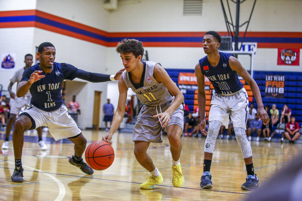 Team Thad's Roman Rubio (11) drives toward the net against New York defenders  Luther Muhammad (1) and  Alan Griffin (10) during the Las Vegas Fab 48 Championship Game on Sunday, July 30, 2017. Te ...