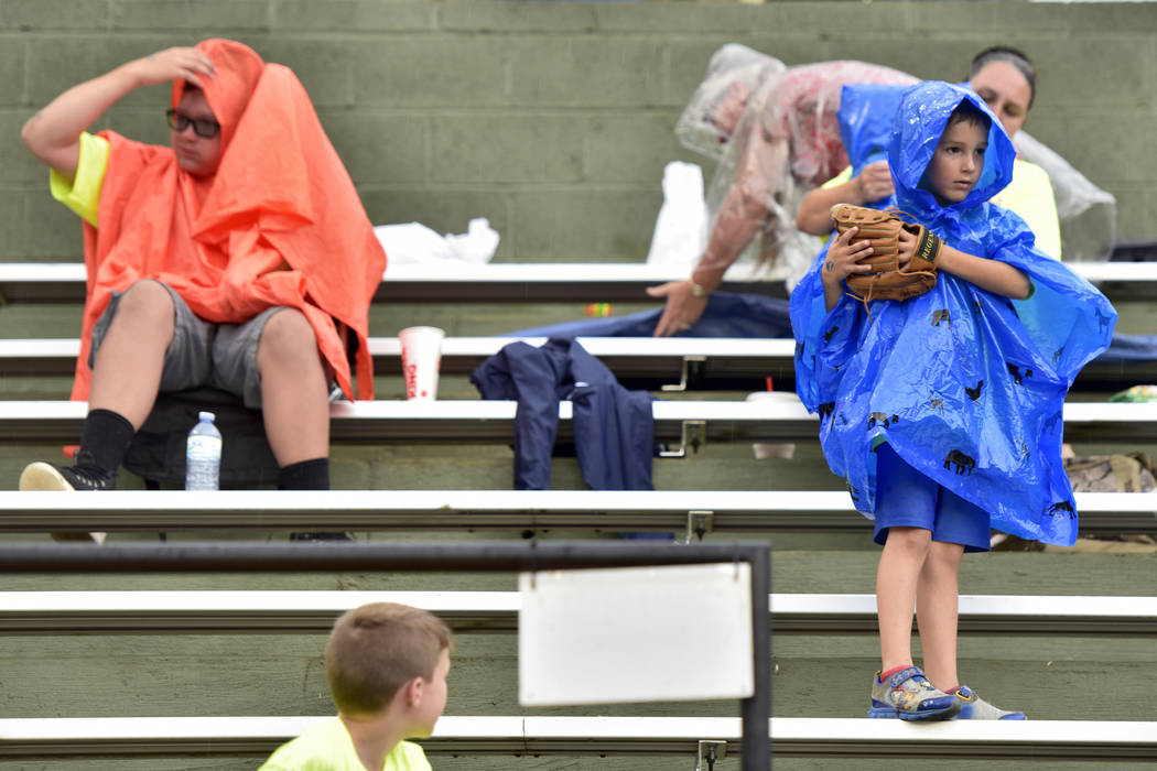 Fans put on their rain gear during game 13 of The American Legion World Series on Monday, August 14, 2017 in Shelby, N.C.. Henderson, Nev., Post 40 defeated Bryant, Ark., Post 298 7-3 in nine-inni ...