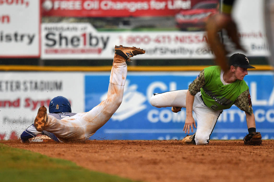 Roger Riley of Henderson, Nev., Post 40 slides safely into second as the ball is thrown wild of Seth Tucker of Bryant, Ark., Post 298 during game 13 of The American Legion World Series on Monday,  ...