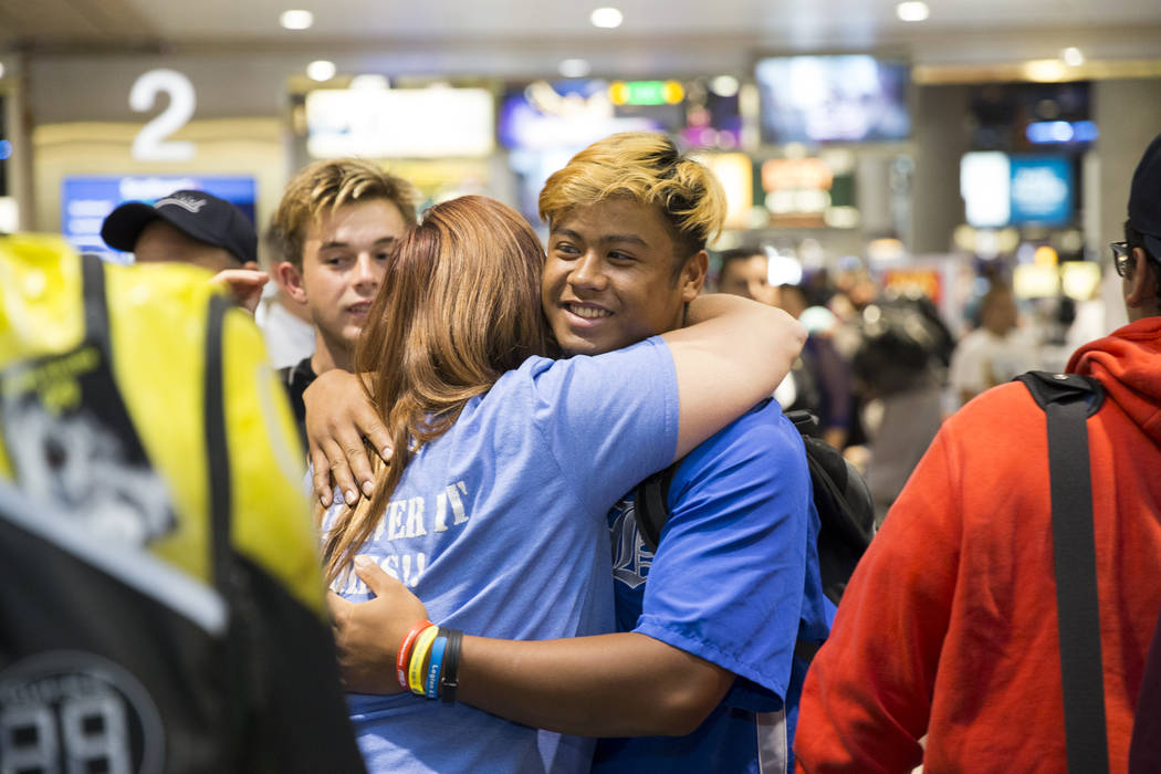 Jaime Riley, left, a mother of a player in the Southern Nevada Blue Sox baseball team, hugs team player Erik Cruz, 19, during the team's arrival to McCarran International Airport after their Ameri ...