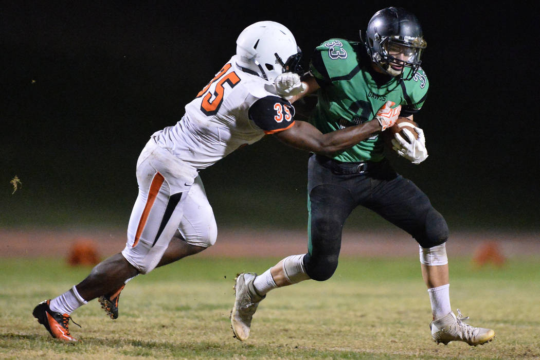 Virgin Valley running back Jayden Perkins (33) tries to shed a tackler during the Virgin Valley High School Chaparral High School High School game at Virgin Valley High School in Mesquite, Nev., o ...