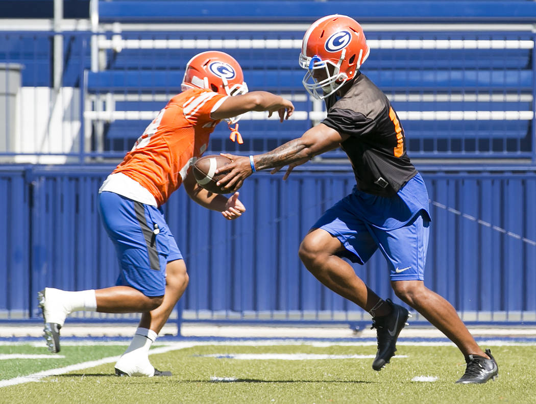 Bishop Gorman quarterback Dorian Thompson Robinson, right, hands the ball off to a teammate during practice at Fertitta Field at Bishop Gorman High School Monday, Aug. 21, 2017, in Las Vegas. Brid ...