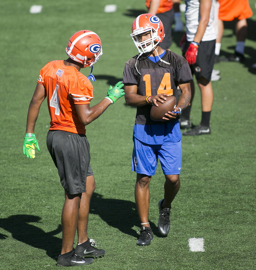 Bishop Gorman quarterback Dorian Thompson Robinson, right, talks with teammate Cedric Tillman during practice at Fertitta Field at Bishop Gorman High School Monday, Aug. 21, 2017, in Las Vegas. Br ...