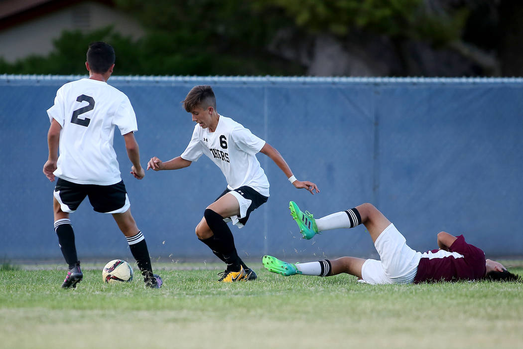 Palo Verde players Cole Lawrence, left, and Antonio Gomez take the ball as Faith Lutheran player Abel Mendoza is knocked to the ground during a game at Green Valley High School on Monday, Aug. 28, ...